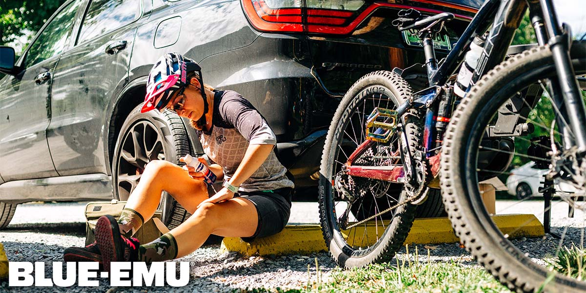 Image of Annmarie Wolfe mountain biker and women's advocate applying Blue-Emu Continuous Pain Relief Spray to her knee beside her mountain bike