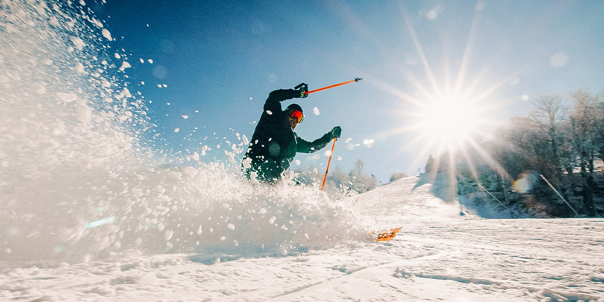 Image of Anthony Horne skiing down a snow slope with snow spraying up