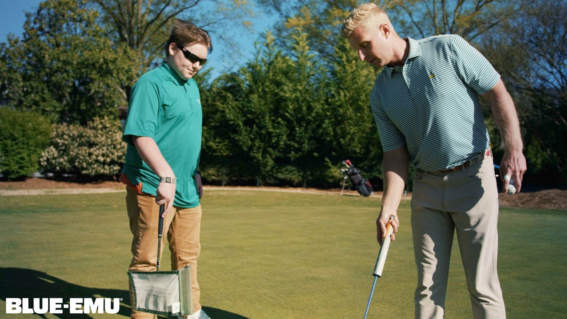 Image of Chase Vicars teaching a boy how to play golf as part of his charity Golf Impact