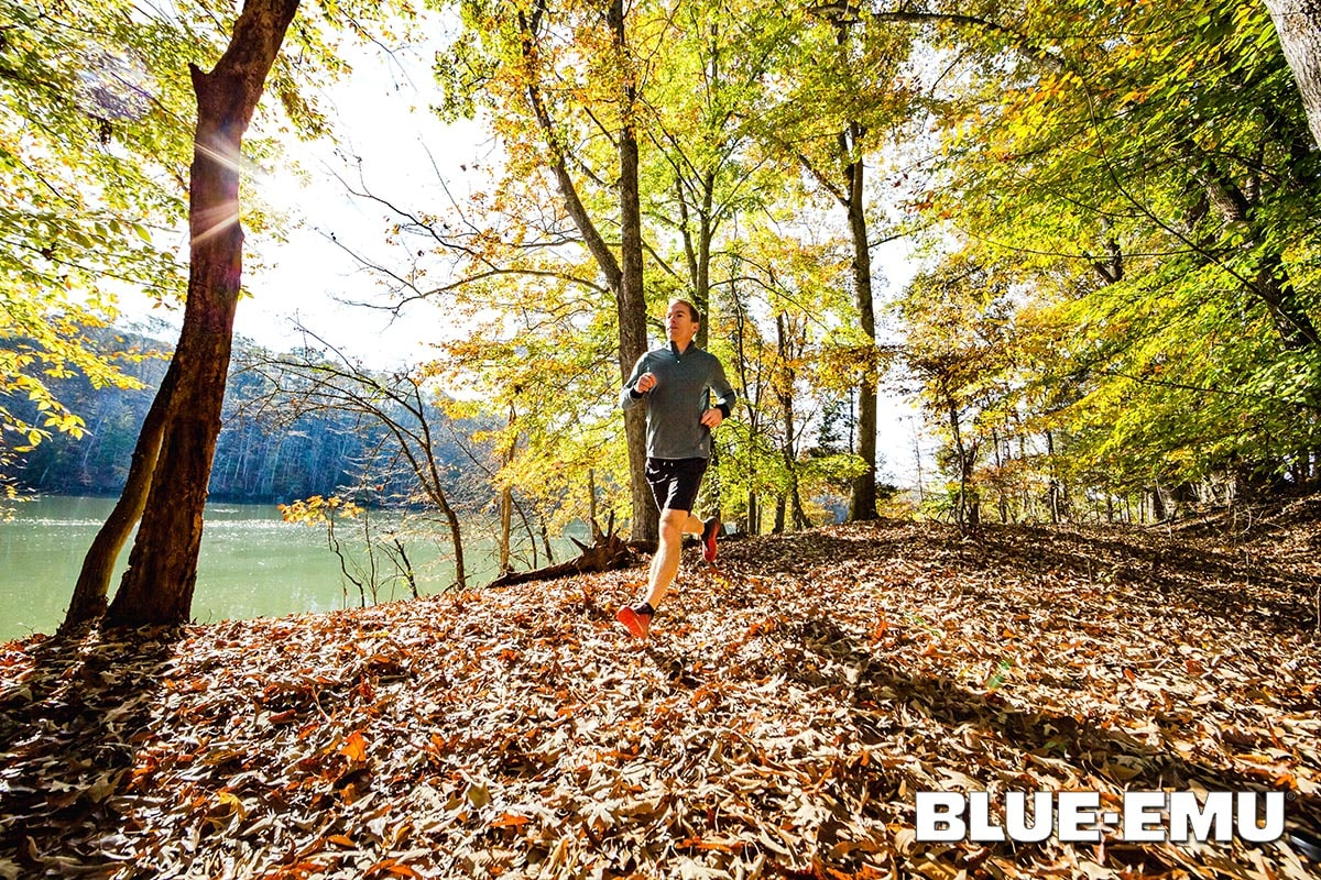Image of a man running on a trail with fall foliage and sun shining through the trees