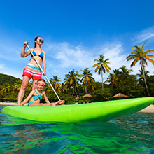 Image of a woman in a bikini on a paddle board with her daughter in a bathing suit paddling by a tropical beach with palm trees