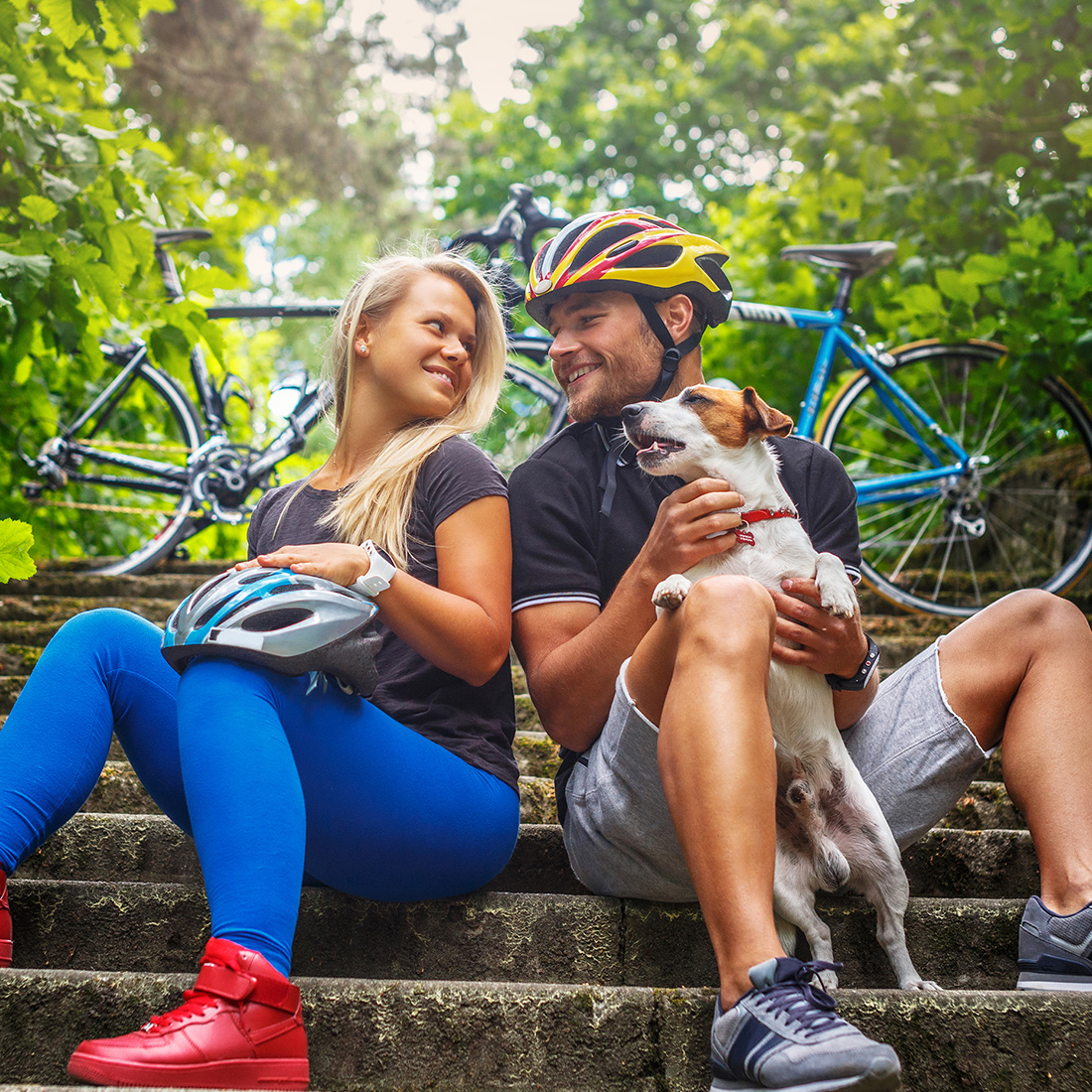 Image of a young couple sitting with their dog in front of a bike on a stair after a long and fun bike ride