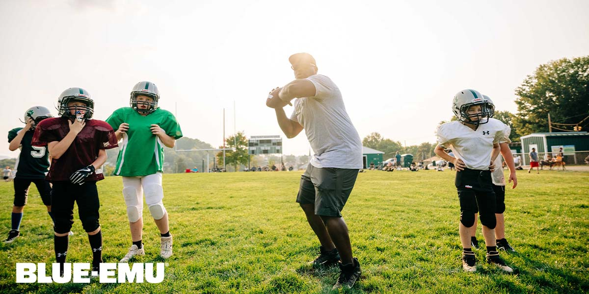 Image of youth football coach Bryant Rutledge demonstrating how to throw a football pass to his team