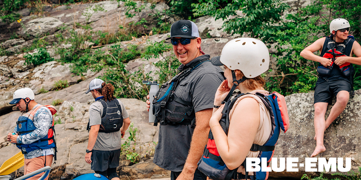 Image of Jubal Roe USA Rafting Guide talking with a client on the river bank before heading out on the water