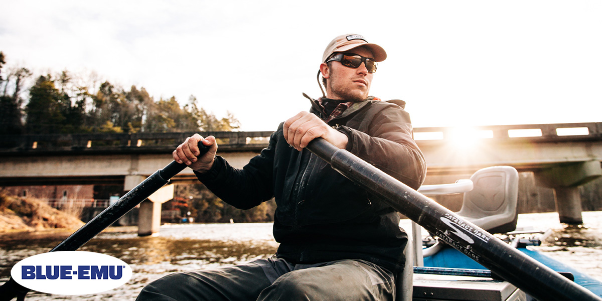 Image of Guide Matt Reilly rowing a boat under an overpass while taking clients fly fishing on a local river