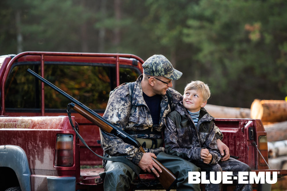 Image of a Grandfather with his grandson in camo sitting on a truck tailgate getting ready to go hunting